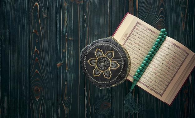 Offener koran mit rosenkranzperlen und muslimischem hut