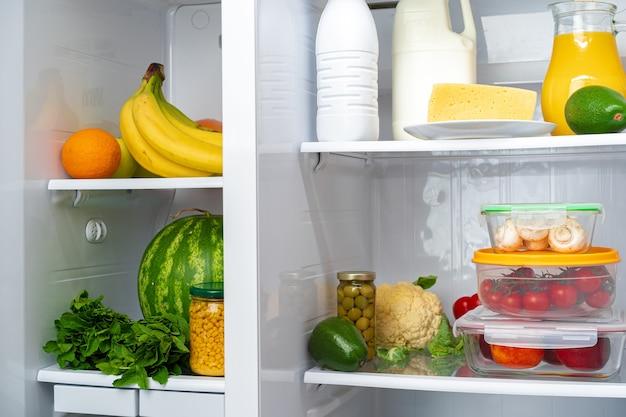 Offener kühlschrank mit frischem obst, gemüse und getränken