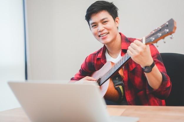 Offener laptop des jungen asiatischen jugendlichjungen für suchlied und das spielen der klassischen gitarre