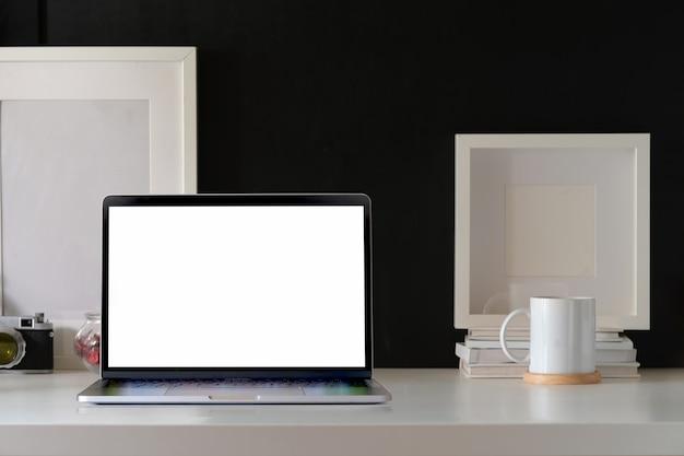 Offener laptop des modells auf weißem minimalem arbeitsplatzschreibtisch