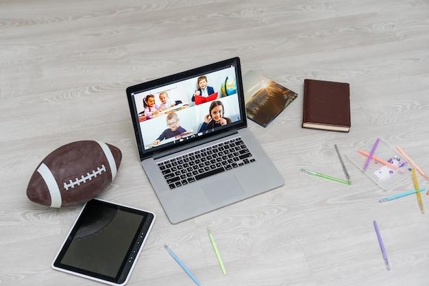 Offener laptop mit fußball oder rugbyball auf dem boden, videochat