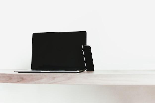 Offener laptop mit smartphone auf holztisch arbeiten von zu hause während covid19