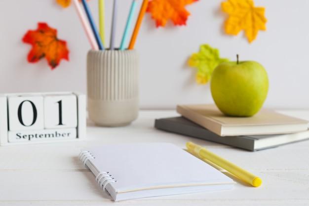 Offener notizblock mit stiftnotizbüchern bleistiften und grünem apfel und kalender vom 1. september auf dem tisch