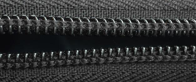Offener reißverschluss an einem schwarzen rucksack, nahaufnahmetextil, bannerfoto
