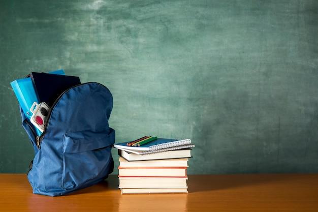 Offener rucksack mit stapel büchern