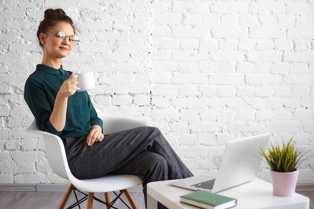 Offener schuss der modischen jungen freiberuflerin, die runde brillen und haarknoten trägt, die kaffee oder tee am coworking space genießen, im stuhl vor offenem tragbarem computer sitzen, lächelnd