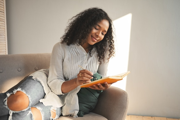 Offener schuss des bezaubernden hübschen mädchens des gemischten aussehens, das lächelt, während gedichte schreibt, verliebt ist, ihre gedanken und geheimnisse mit tagebuch teilt. menschen-, lifestyle- und freizeitkonzept