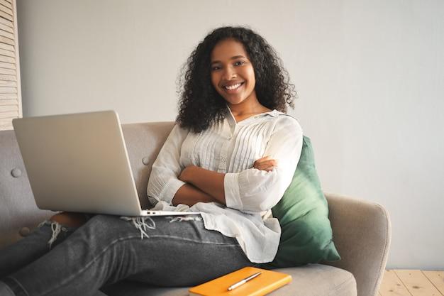 Offener schuss des glücklichen erfolgreichen jungen dunkelhäutigen weiblichen bloggers, der auf sofa mit modernem elektronischem gerät auf ihrem schoß sitzt, arme verschränkt hält und selbstbewusst lächelt, internet surft