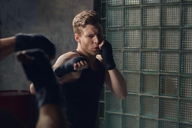 Offener schuss des hübschen jungen mannes mit stoppeln, die nicht erkennbaren gegner kämpfen. zwei männliche boxer trainieren zusammen, kämpfen drinnen und tragen schwarze gummibänder an den handgelenken. selektiver fokus