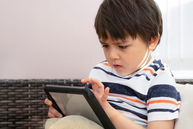 Offener schuss des schulkindes spiel auf tablette mit ernstem gesicht, geernteter schuss kinderjunge konzentrierte sich aufpassende karikatur auf notenauflage, das kind, das sich zu hause am wochenende entspannt.