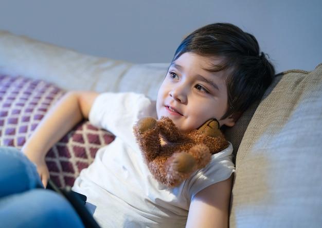 Offener schuss eines glücklichen jungen mit lächelndem gesicht, der auf dem sofa sitzt und fernsieht, positives kind, das auf der couch liegt und mit hundespielzeug spielt. ehrliches erschossenes gesundes kind, das sich am wochenende zu hause entspannt.