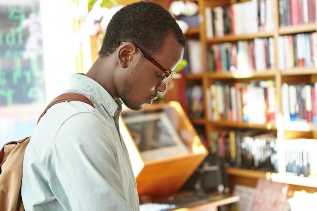 Offener schuss eines konzentrierten schwarzen europäischen männlichen studenten mit rucksack, der an der forschung in der universitätsbibliothek arbeitet. stilvoller dunkelhäutiger mann, der phrasenbuch in buchhandlung vor ferien im ausland sucht