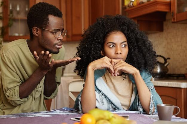 Offener schuss eines unglücklichen jungen afroamerikanischen paares, das zu hause streit hat: schuldiger, bedauernder mann mit brille, der seine wütende frau um vergebung bittet und sich bei ihr entschuldigt, weil sie einen schlechten fehler gemacht hat