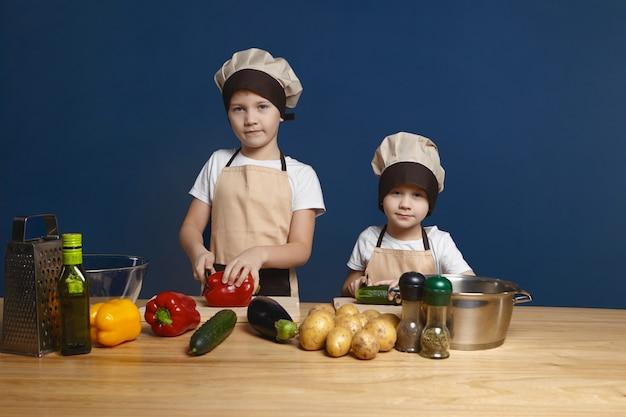 Offener schuss von zwei männlichen kindern, die kochmützen und schürzen tragen, die zusammen am küchentisch das mittagessen machen