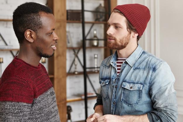 Offener schuss von zwei stilvollen männlichen besten freunden verschiedener rassen, die sich gegenüberstehen