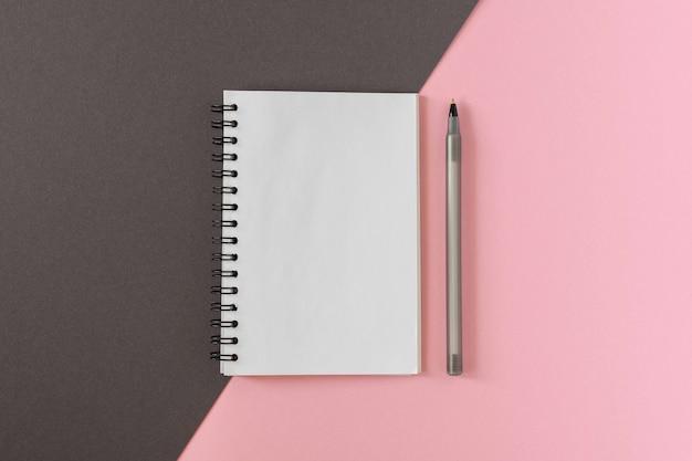 Offener spiralblock auf farbigem hintergrund, notizbuch und stift liegen auf strukturpapieren, flaches laienkonzept