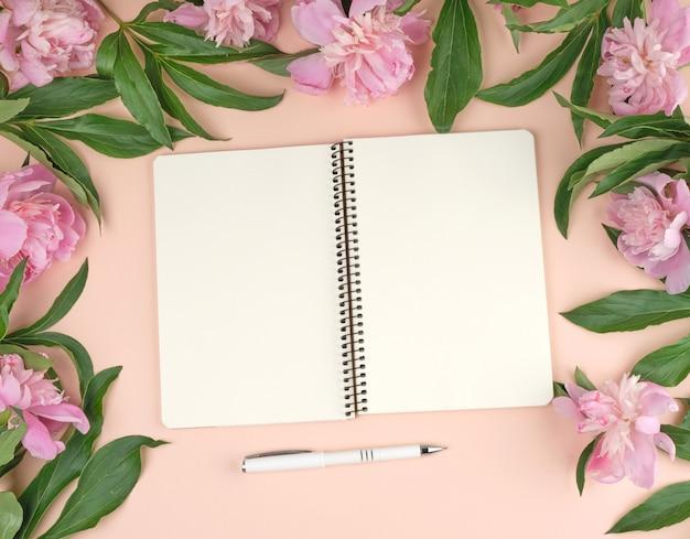 Offener spiralblock mit weißen leeren blättern und einem strauß rosa pfingstrosen