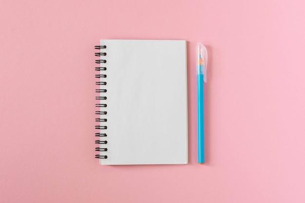 Offener spiralnotizblock an einer rosa wand, notizbuch und stift liegen auf strukturpapier