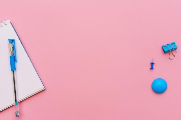 Offener spiralnotizblock auf rosa hintergrundnotizblock und blauer stift liegen auf papierflachkonzept flat