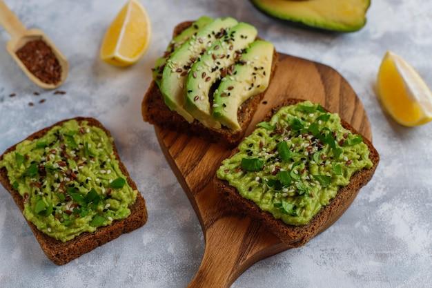 Offener toast der avocado mit avocadoscheiben, zitrone, leinsamen, samen des indischen sesams, schwarzbrotscheiben, draufsicht