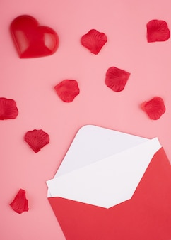Offener umschlag mit leeren, herz- und rosenblättern auf rosa hintergrund