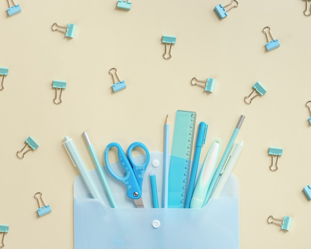 Offener umschlag und schulmaterial, bleistifte, kugelschreiber, lineale, blauer farbton