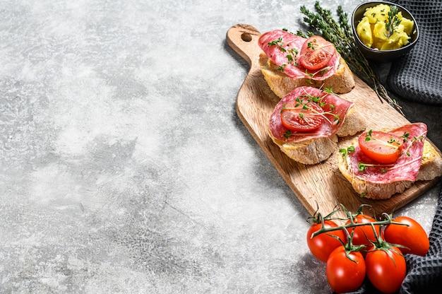Offenes baguette-sandwich mit salami-salchichon, kirschtomaten und mikrogrün. draufsicht. speicherplatz kopieren