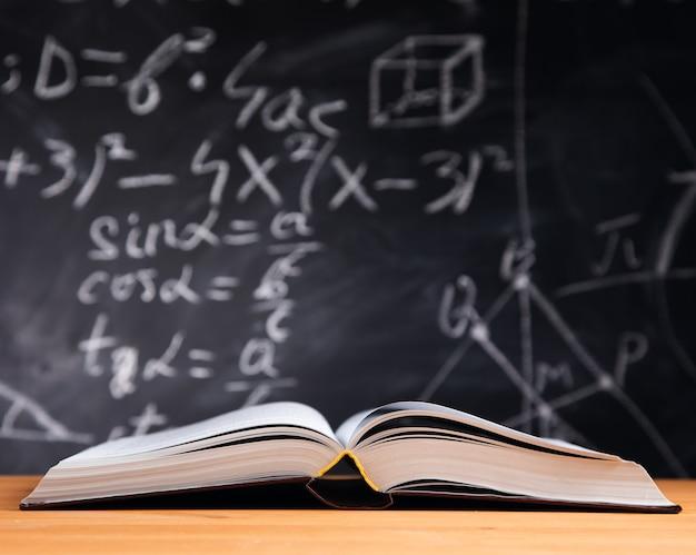 Offenes buch auf dem tisch im klassenzimmer mit tafelhintergrund