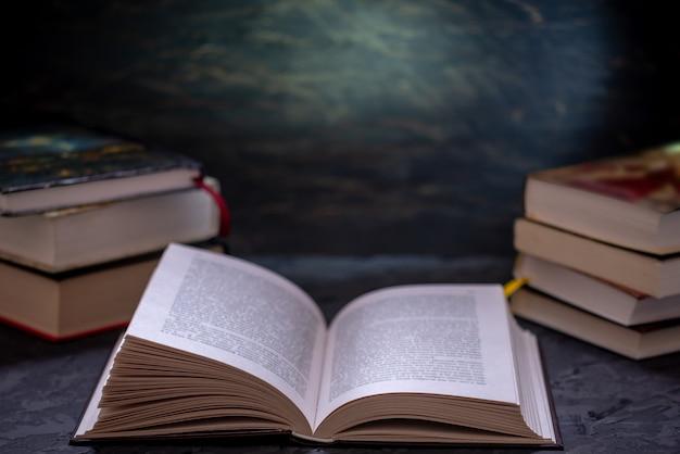 Offenes buch auf einem stapel büchern auf einer tabelle. bildung und lesen von papierbüchern