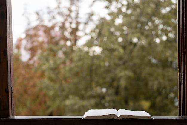 Offenes buch auf einer vintage-fensterbank. lesen und ausruhen