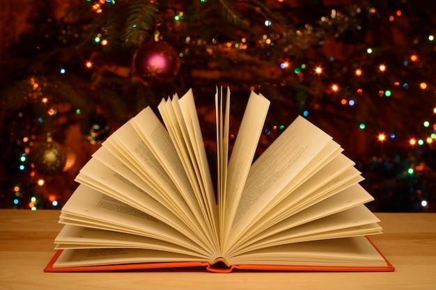 Offenes buch auf tisch mit geschmücktem weihnachtsbaum auf der