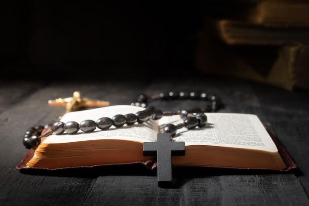 Offenes buch der bibel und des kruzifixes auf dunkler tabelle. zurückhaltendes bild des neuen testaments, des kreuzes und des rosenkranzes im hellen licht unter dunkelheit und schatten, großaufnahme