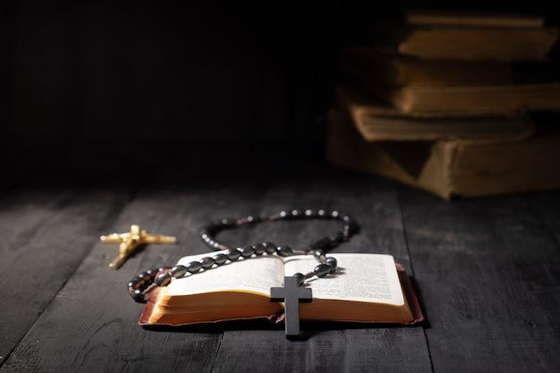 Offenes buch der bibel und des kruzifixes auf dunkler tabelle. zurückhaltendes bild des neuen testaments, des kreuzes und des rosenkranzes im hellen licht unter dunkelheit und schatten mit kopienraum