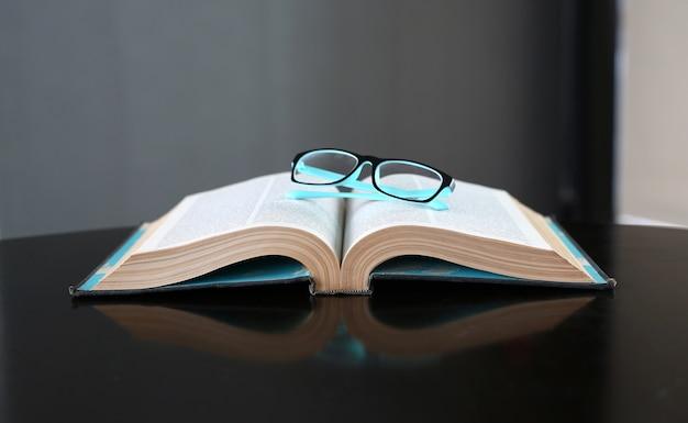 Offenes buch, hardcover bücher und gläser auf holztisch. bildungshintergrund.