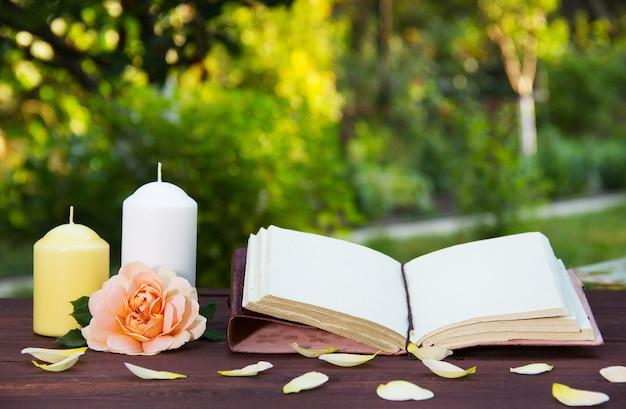 Offenes buch, kerze und duftende rose. romantisches konzept.