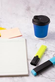 Offenes buch leere notizbuchseite, blauer textmarker, haftnotiz und blaue tasse kaffee auf weißem marmortisch. schreibtisch aus marmor. schablone. hintergrund.