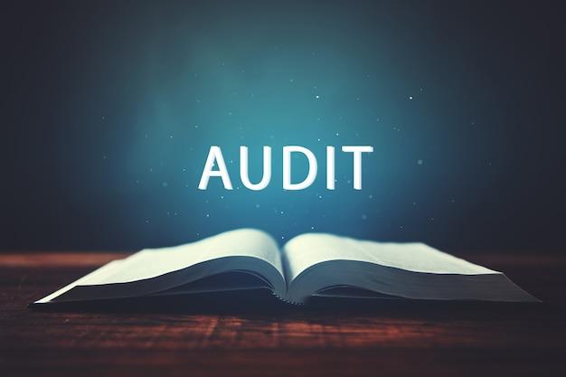 Offenes buch mit audit-inschrift auf dunkler oberfläche