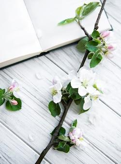 Offenes buch mit blütenzweig des apfelbaums auf weißem holztisch.