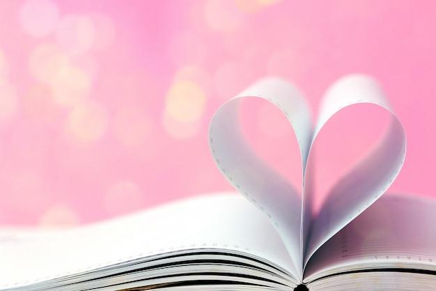 Offenes buch mit herzform auf hellem bokeh rosahintergrund. valentinstag-konzept. minimaler stil.
