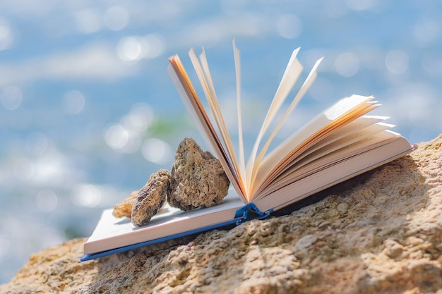 Offenes buch mit kleinen steinen an der steinküste des meeres