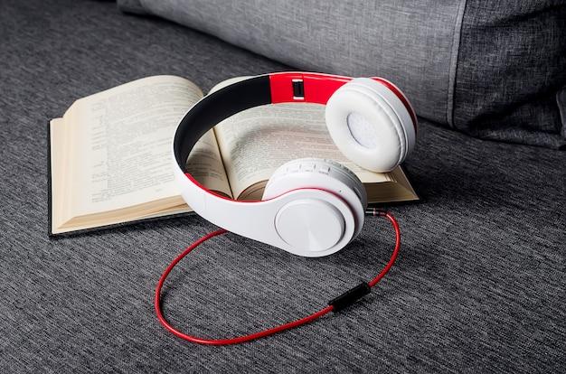 Offenes buch mit kopfhörern auf grauem sofa. hörbuchkonzept. moderne bildung, lesen