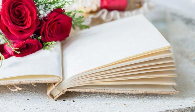 Offenes buch mit leerseiten und details der roten rosen