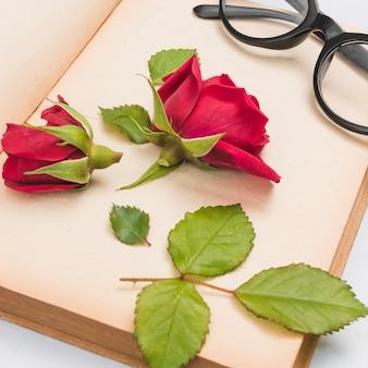 Offenes buch, rose und gläser