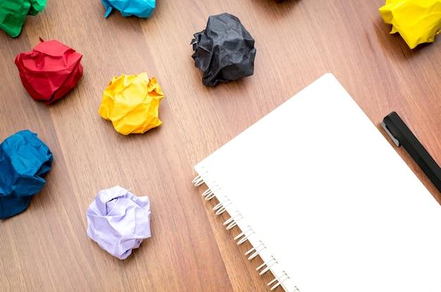 Offenes buch und bleistift mit gruppe des bunten zerknitterten papierballs