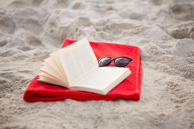 Offenes buch und sonnenbrille gehalten auf roter serviette
