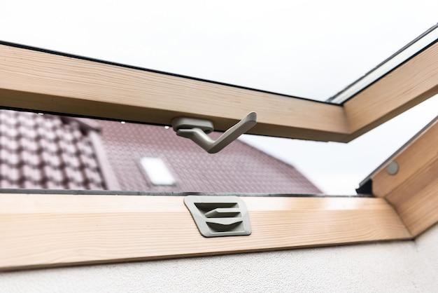 Offenes dachfenster aus holz mit blick auf die straße