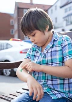 Offenes erschossenes kind, das auf bank sitzt und grünes glitzern auf seinem arm betrachtet, kindjunge, der draußen spielt und allein mit verschwommenen autos auf der straße im sonnigen sommer spielt