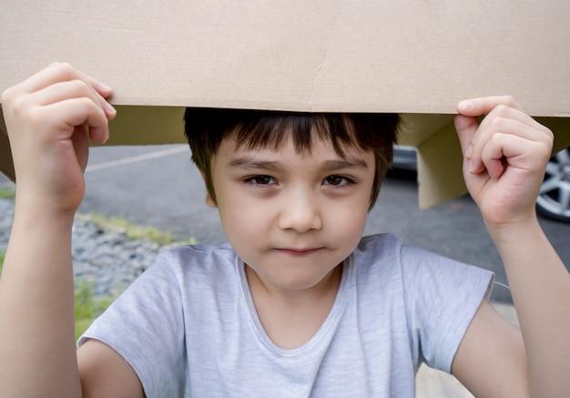 Offenes erschossenes kind, das pappkarton auf seinen kopf setzt