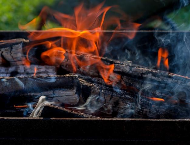 Offenes feuer, rauch, flamme von brennendem brennholz im grill. heiße kohlen für döner in der natur