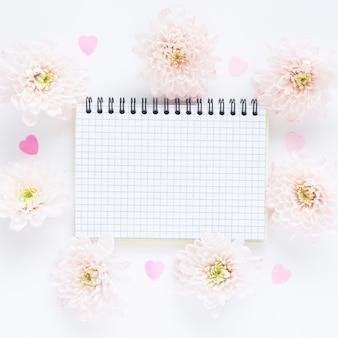 Offenes kariertes notizbuch auf einer quelle und sanft rosa blüten von chrysanthemen und plastikherzen